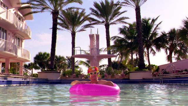 Senior woman in sunglasses + bathing cap relaxing in pink inner tube in pool / palm trees in background