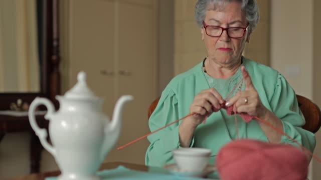 Senior woman knitting during tea time at home.