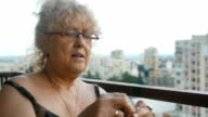 Senior woman knitting on a city balcony