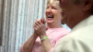 Senior Woman Laughs while Dining with Friends