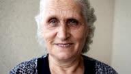 Senior woman looking at camera and smiling. Hand-held shot