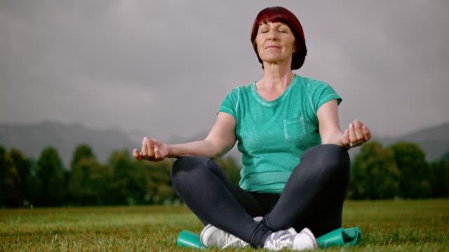 SLO MO DS Senior Kvinna mediterar i parken