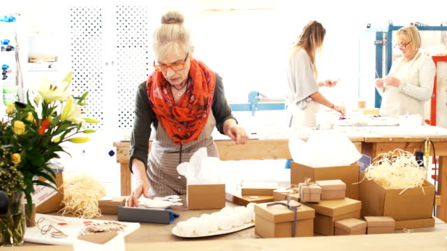 Senior woman packs goods for online orders looks up and smiles to camera