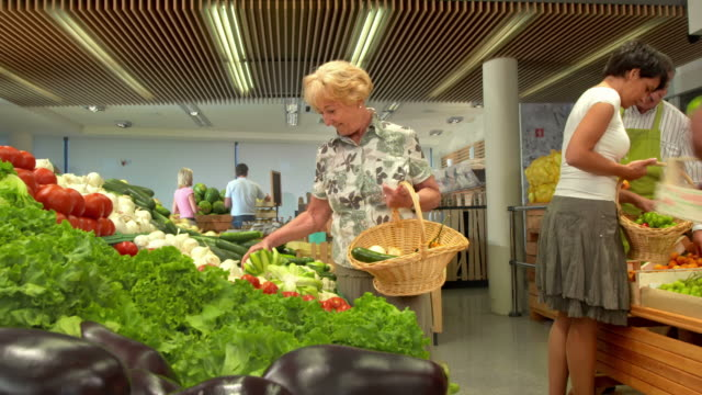HD DOLLY: Senior Woman Picking Up Vegetables