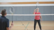 Senior woman playing indoor badminton with her male friend