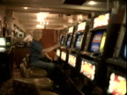 WS, Senior woman playing on slot machine, Reno, Nevada, USA