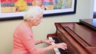 MS Senior woman playing piano / Portland, Oregon, USA