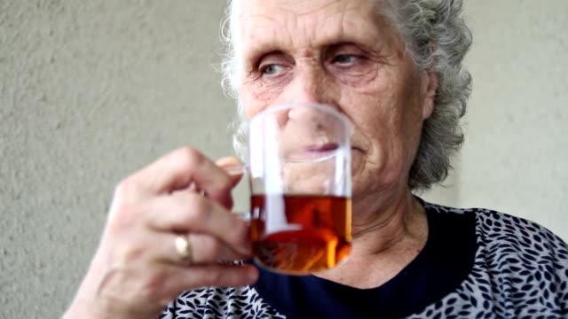 Senior woman portrait looking around and drinking tea