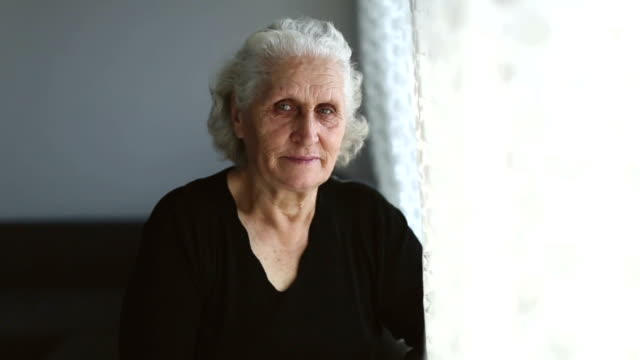 Senior woman portrait looking at camera and then through window behind the curtain