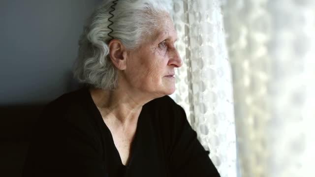 Senior woman portrait looking through window behind the curtain
