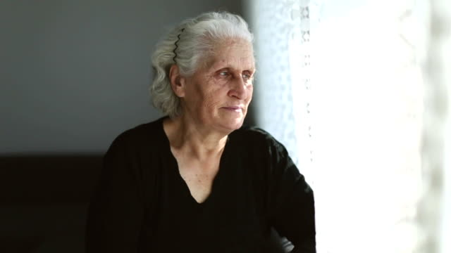 Senior woman portrait looking through window behind the curtain with positive expression