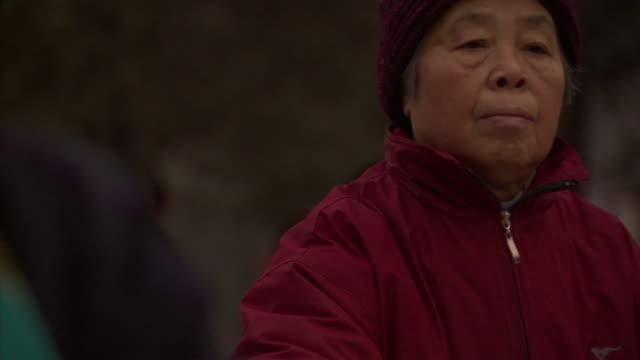 SLO MO CU SELECTIVE FOCUS Senior woman practicing tai chi in public park, Beijing, China