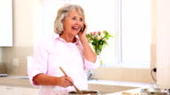 Senior woman preparing a meal and answering phone