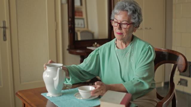 Senior vrouw lezen van een boek tijdens de middag thee thuis.