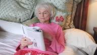 MS Senior woman reading magazine in bed / Portland, Oregon, USA