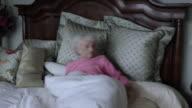 MS ZI Senior woman reading magazine in bed / Portland, Oregon, USA