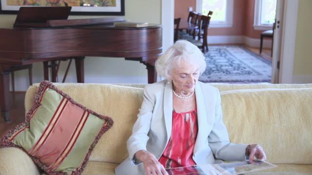 MS Senior woman reviewing photo album in living room / Portland, Oregon, USA