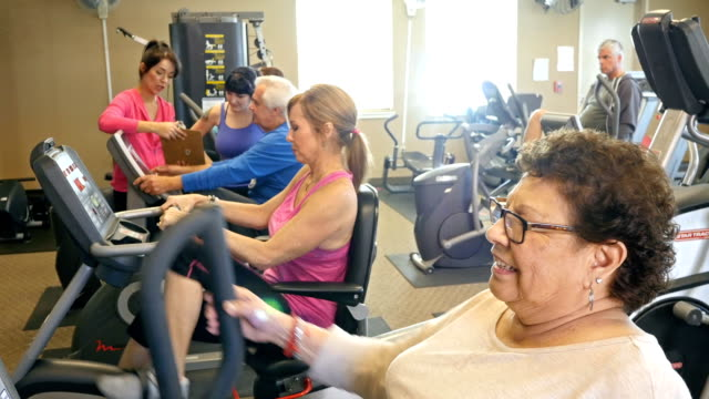 Senior woman riding bicycle at health club
