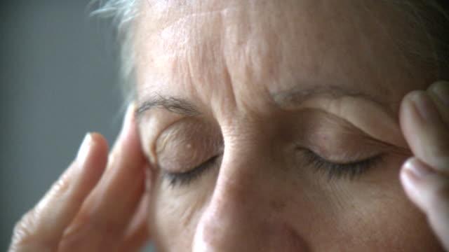 ECU SELECTIVE FOCUS Senior woman rubbing temples, New York City, New York, USA