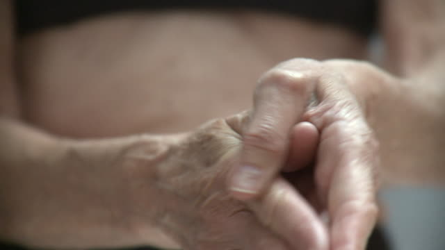 ECU SELECTIVE FOCUS Senior woman rubbing wrist and thumb, New York City, New York, USA
