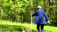Senior Woman Running with Dog