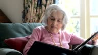 Senior woman sits in armchair at home and looks through photo album whilst smiling nostalgically