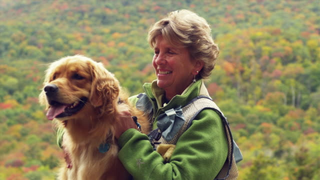 CU Senior woman sitting and patting Golden Retriever dog outdoors, Manchester, Vermont, USA