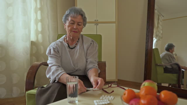 Senior woman sitting at home and taking a pill with a glass of water.