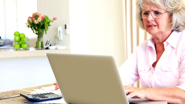 Senior woman sitting at table paying her bills with laptop