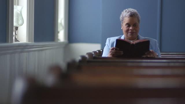 MS PAN Senior woman sitting down in church pew and reading Bible near window / Port Gamble, Washington State, USA