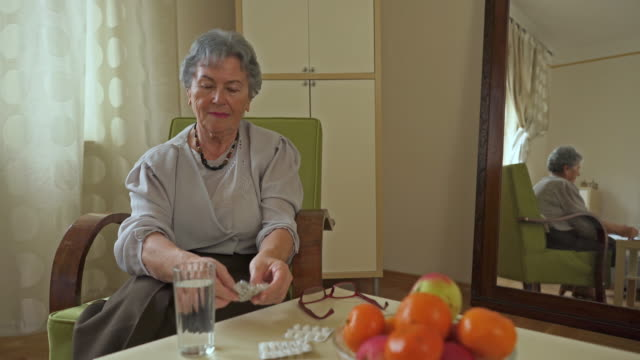 Senior woman sitting in armchair at home and taking medicine with glass of water.