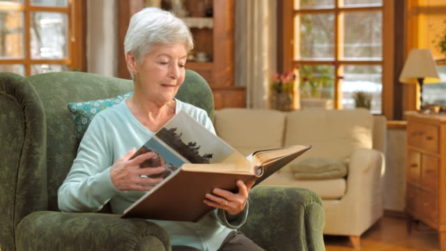 Senior woman sitting in chair and looking at photo album
