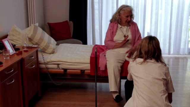 Senior Woman sitting on bed in a nursery home and chatting with a nurse.