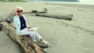 WS ZI Senior woman sitting on driftwood reading book / Portland, Oregon, USA