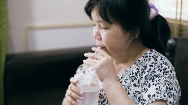 Senior vrouw zittend op de Bank en drinkwater