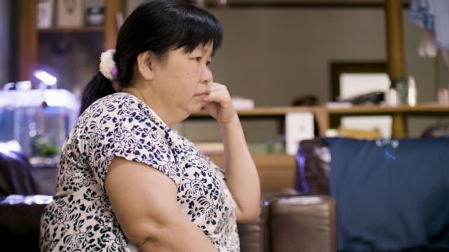 Senior vrouw zittend op de Bank en TV kijken