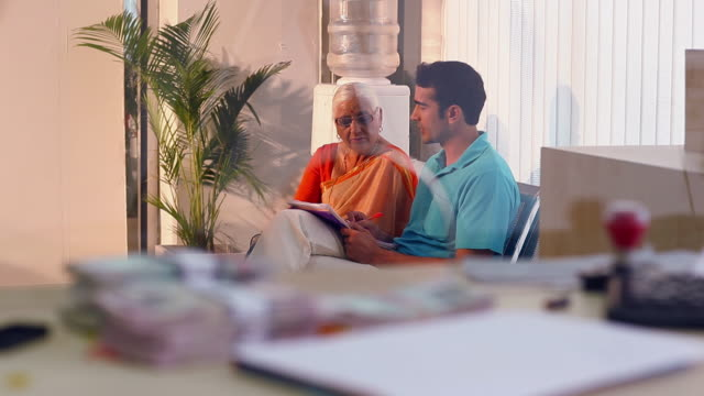 Senior woman sitting with his son sittin at bank lobby, Delhi, India