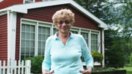 MS Senior woman standing in front of house and smiling / Manchester, Vermont, USA.