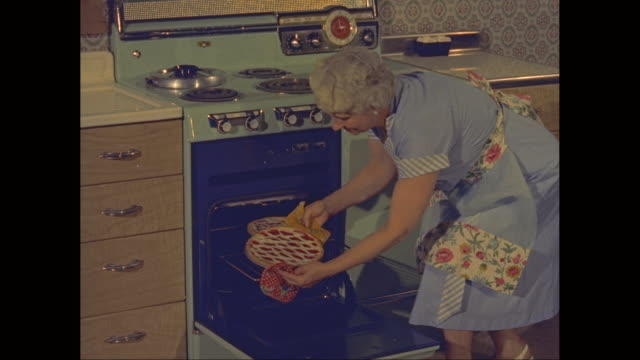 MS Senior woman taking cherry pie from the oven / United States