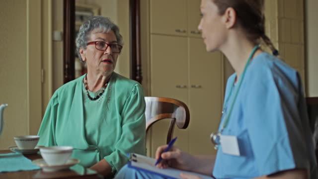Senior vrouw praten met home verzorger en het thuis drinken van thee.