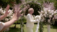 SLO MO MS Senior woman tossing bouquet to wedding guest at outdoor wedding / Los Angeles, California, USA