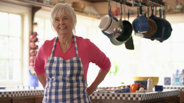 MS Senior woman tying on an apron in her kitchen