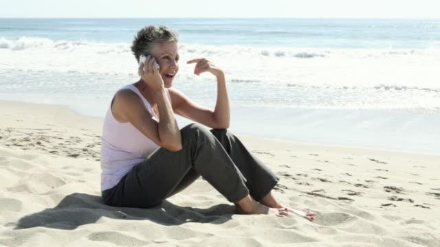 Senior woman using cell phone on beach