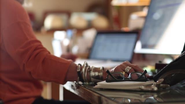 Senior woman using desktop computers in her office