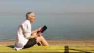 Senior vrouw met behulp van digitale tablet op strand