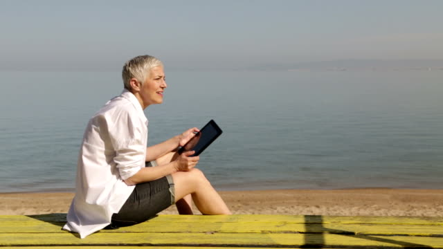 Senior woman using digital tablet at beach