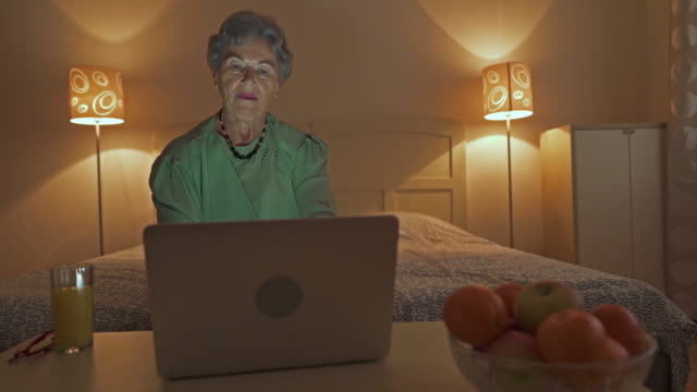 Senior woman using laptop and surfing the net at home.