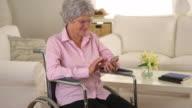 Senior woman using smartphone in wheelchair