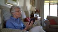 Senior woman video conferencing on digital tablet