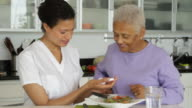 Senior woman with caregiver taking medication